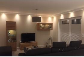 Deckenprofil BSKL-180A-PR für die direkte Beleuchtung der Wand mit LED Strahlern in einem Wohnzimmer.