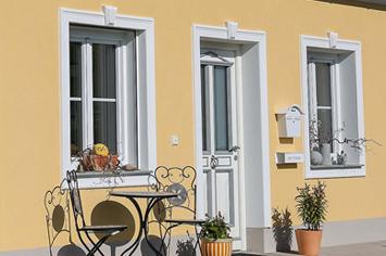 Klassische Gestaltung der Fassade mit Fensterfaschen und Schlussstein mit gelber Fassade