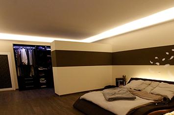 Eine stilvolle indirekte Beleuchtung der Decke im Schlafzimmer mit Fotowand